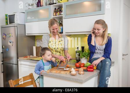 Mutter und Sohn Gitter Gemüse, während Tochter am Telefon sprechen - Stockfoto