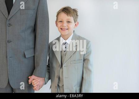 Vater und Sohn Hand in Hand vor weißem Hintergrund - Stockfoto