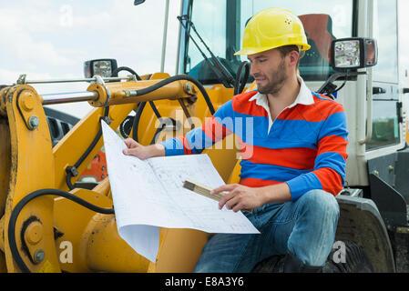 Bauarbeiter sitzen auf Bagger mit Bauplan - Stockfoto