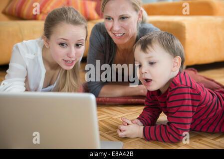Familie mit Laptop im Wohnzimmer, Lächeln - Stockfoto
