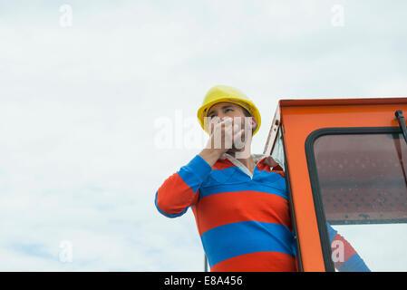 Bauarbeiter auf der Baustelle mit Bagger - Stockfoto