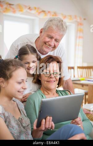 Großeltern und Enkelinnen im digital-Tablette, Lächeln - Stockfoto