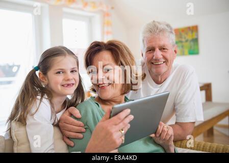 Großeltern und Enkeltochter suchen in digital-Tablette, Lächeln - Stockfoto