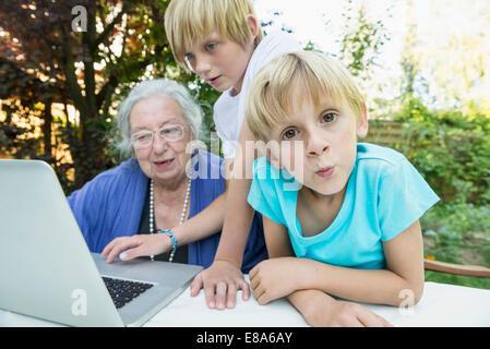 Großmutter und ihre beiden Enkel mit laptop - Stockfoto