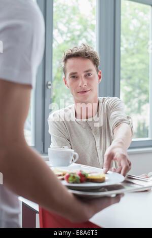 Junger Mann bietet Platte mit Frühstück mit einem anderen Mann, Lächeln - Stockfoto