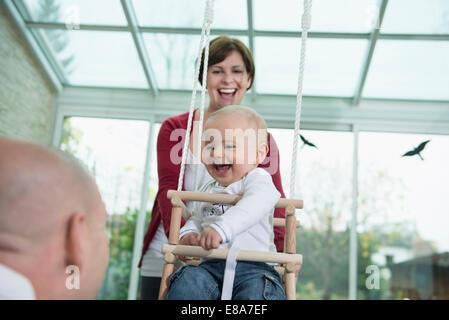 Glücklich Kleinkind sitzt in einem Schwung - Stockfoto