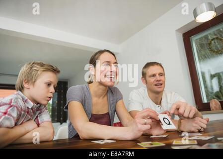Familie im Wohnzimmer zusammen Gesellschaftsspiel spielen - Stockfoto