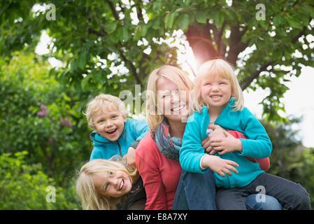 Mutter mit drei kleinen Kindern im Garten spielen - Stockfoto