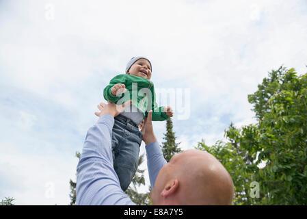 Vater hielt Babyjungen in Armen spielen fliegen - Stockfoto