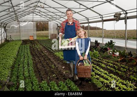 Vater und Tochter, die Ernte von Gemüse im Gewächshaus - Stockfoto