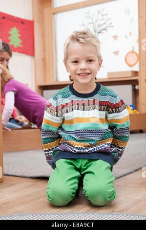 Porträt von glücklich kleiner Junge sitzt in seinem kindergarten - Stockfoto