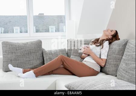Porträt der lächelnde junge Frau mit Tasse entspannend auf Couch zu Hause - Stockfoto