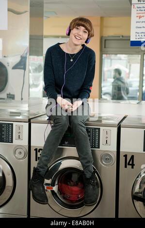 Junge Frau Musik hören auf Waschmaschine, Lächeln - Stockfoto