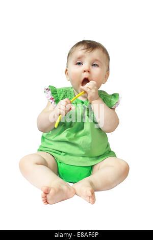 Kind legt gelbe Löffel in den Mund isoliert auf weißem Hintergrund - Stockfoto