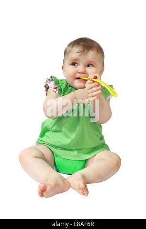 Kind sitzt mit Löffel im Mund isoliert auf weißem Hintergrund - Stockfoto