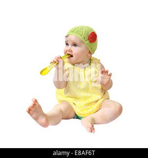 Kleinkind sitzt und halten Löffel im Mund isoliert auf weißem Hintergrund - Stockfoto