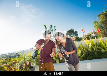 Paar Eröffnung Champagner in Penthouse-Dachgarten, La Jolla, Kalifornien, USA - Stockfoto