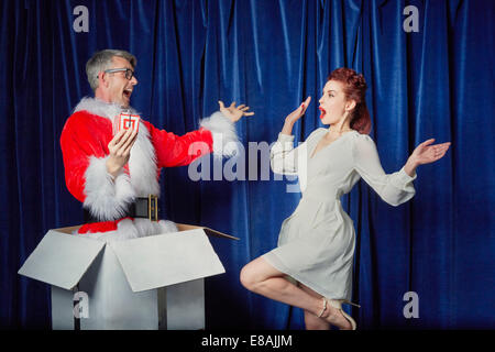 Überraschende Weihnachtsfrau mit Weihnachtsgeschenk - Stockfoto