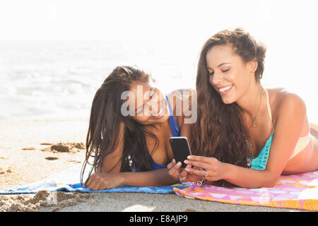 Zwei junge Frauen, Sonnenbaden und Blick auf Smartphone am Strand von Malibu, Kalifornien, USA