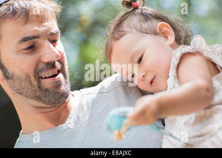 Nahaufnahme von Vater und Kind Tochter hält Wellensittich Sittich im zoo - Stockfoto