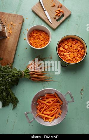 Gehackt, in Scheiben geschnitten, geraspelt und Bund Karotten auf Küchentisch - Stockfoto