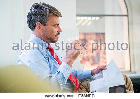 Reife Geschäftsmann Schreibarbeit im Café lesen - Stockfoto