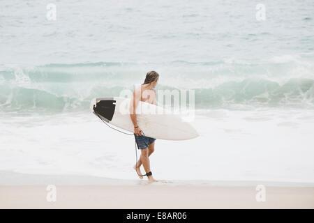 Australische Surfer mit Surfbrett am Strand - Stockfoto