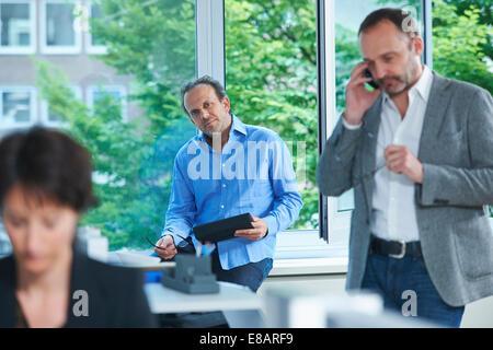 Drei Kollegen im geschäftigen Büro arbeiten - Stockfoto