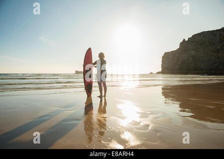 Silhouette senior Frau stehen am Strand mit Surfbrett, Camaret-Sur-Mer, Bretagne, Frankreich - Stockfoto