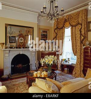 groe spiegel ber dem marmorkamin in gelb wohnzimmer mit opulenten swagged tailed vorhnge am fenster - Gotische Himmelbettvorhnge