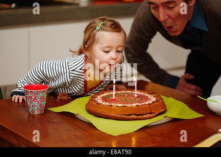Junges Mädchen bläst Geburtstagskerzen auf Kuchen - Stockfoto