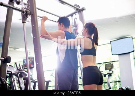 Persönliche Trainer helfen jungen Mann Gewichte heben - Stockfoto
