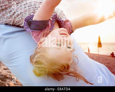 Person mit jungen Mädchen auf Rücken - Stockfoto