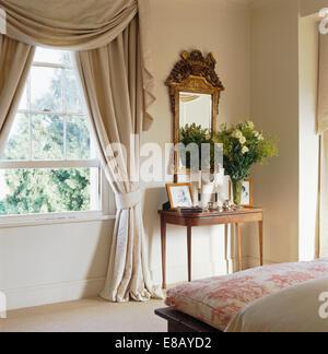 beige seide swagged tailed profilkranz und vorhnge am fenster im land schlafzimmer mit antiker vergoldeter - Gotische Himmelbettvorhnge