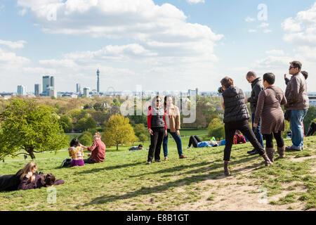 Person fotografieren Freunde auf der Primrose Hill mit der Skyline von London, England, Großbritannien - Stockfoto