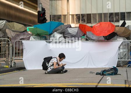 Sicherstellen, dass die äußeren Barrieren werden beobachtet, diese einsame Demonstrant auf ihrem Smartphone ständig - Stockfoto