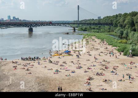 Öffentlicher Strand mit Eisenbahnbrücke auf Hintergrund über Weichsel in Warschau, Polen - Stockfoto