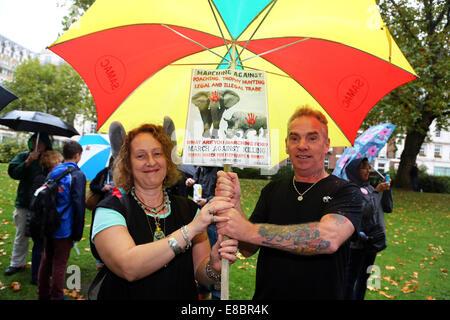 London, UK. 4. Oktober 2014. Demonstranten mit Plakaten, Bannern und Sonnenschirme an den weltweiten Marsch für - Stockfoto