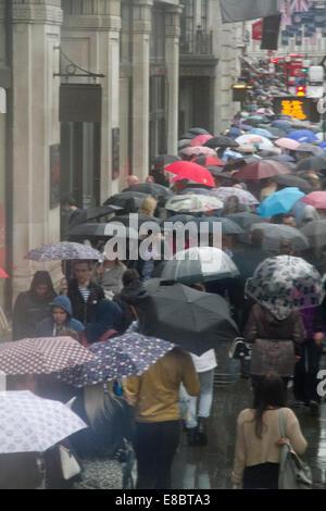 London, UK. 4. Oktober 2014. UK-Wetter. Fußgänger und Käufer Schutz unter Sonnenschirmen in der Oxford Street auf - Stockfoto
