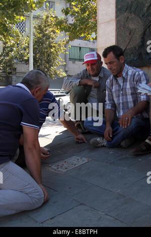 """Männer, die ein Spiel von """"Titzmitz"""" im Schatten der Statue zu unbekannten Partisanen in zentralen Tirana, Albanien - Stockfoto"""