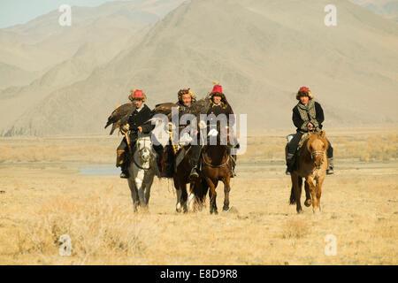Vier kasachischen Adler Jäger auf ihren Pferden auf dem Weg zum Eagle Festival in Sagsai, Bayan-Oelgii-Aimag, Mongolei - Stockfoto