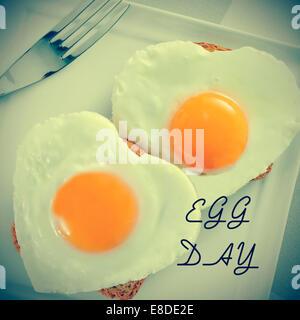 ein paar der herzförmigen Spiegeleier auf Brot und die Text-Ei-Tag für die Welt-Ei-Tag, mit einem Retro-Effekt - Stockfoto
