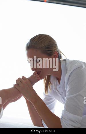 Mutter ihr Baby Füße küssen - Stockfoto