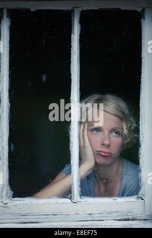 Gelangweilte Frau betrachten das regnerische Wetter durch den Fensterrahmen - Stockfoto