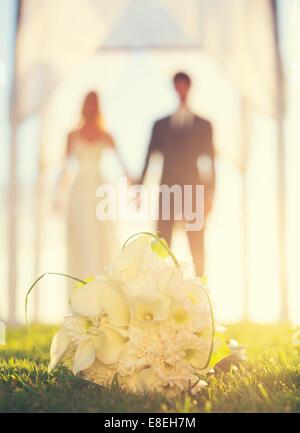 Nahaufnahme der Brautstrauß. Blumen im Mittelpunkt. Braut und Bräutigam im Hintergrund. - Stockfoto
