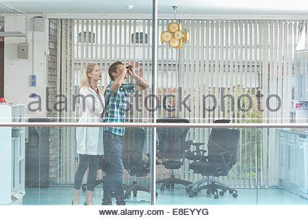 Lächelnder Mann und Frau aus Fenster - Stockfoto