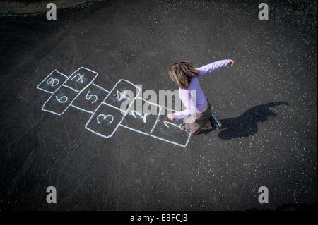 Ein junges Mädchen, Himmel und Hölle auf dem Spielplatz spielen. - Stockfoto