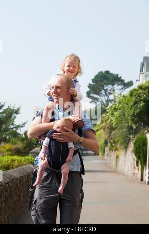 Reife Dad / Vater mit zwei / 2 Kinder; ein Kind auf Schultern und Baby im Tragetuch. Cornwall UK. - Stockfoto