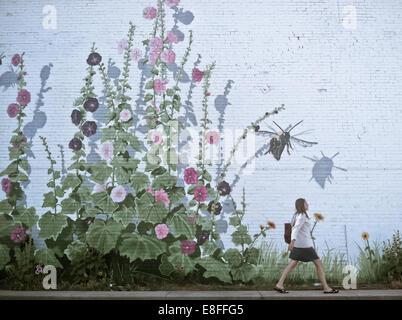 Frau zu Fuß durch blumige Wand - Stockfoto