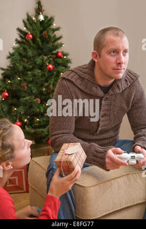 Frau, ein Mann mit Computerspielen Weihnachtsgeschenk geben - Stockfoto